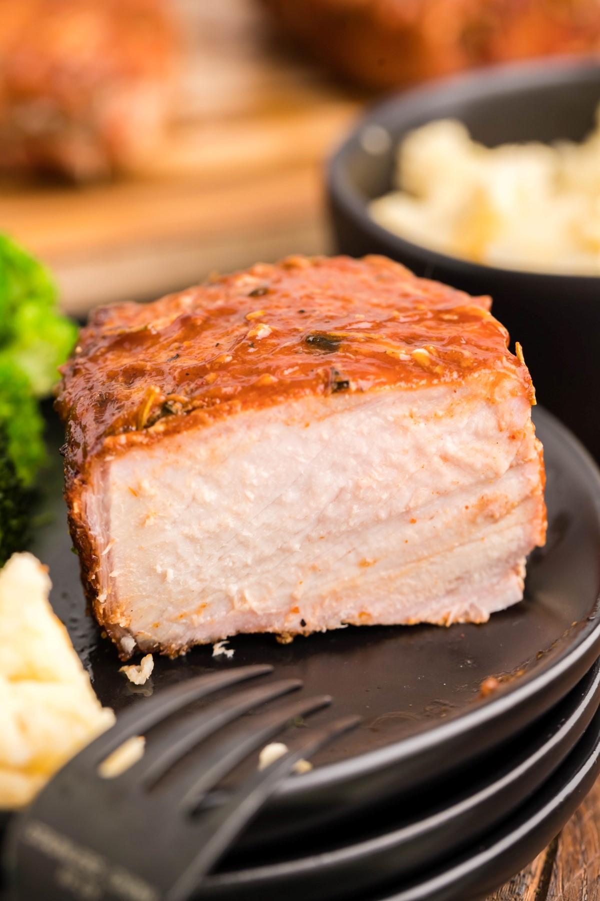 Smoked pork chop cut in half on a black plate.