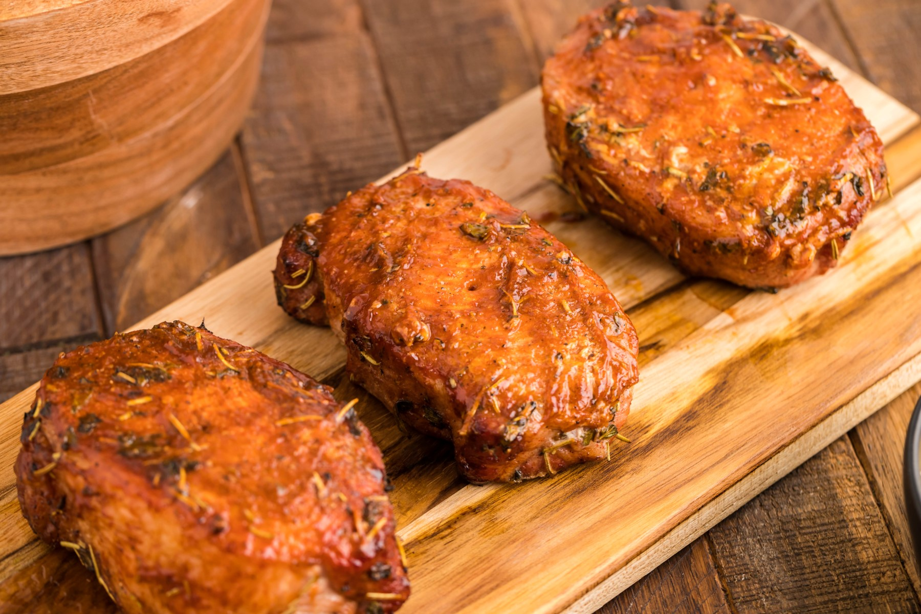 Smoked pork chops on a wooden board covered in BBQ sauce