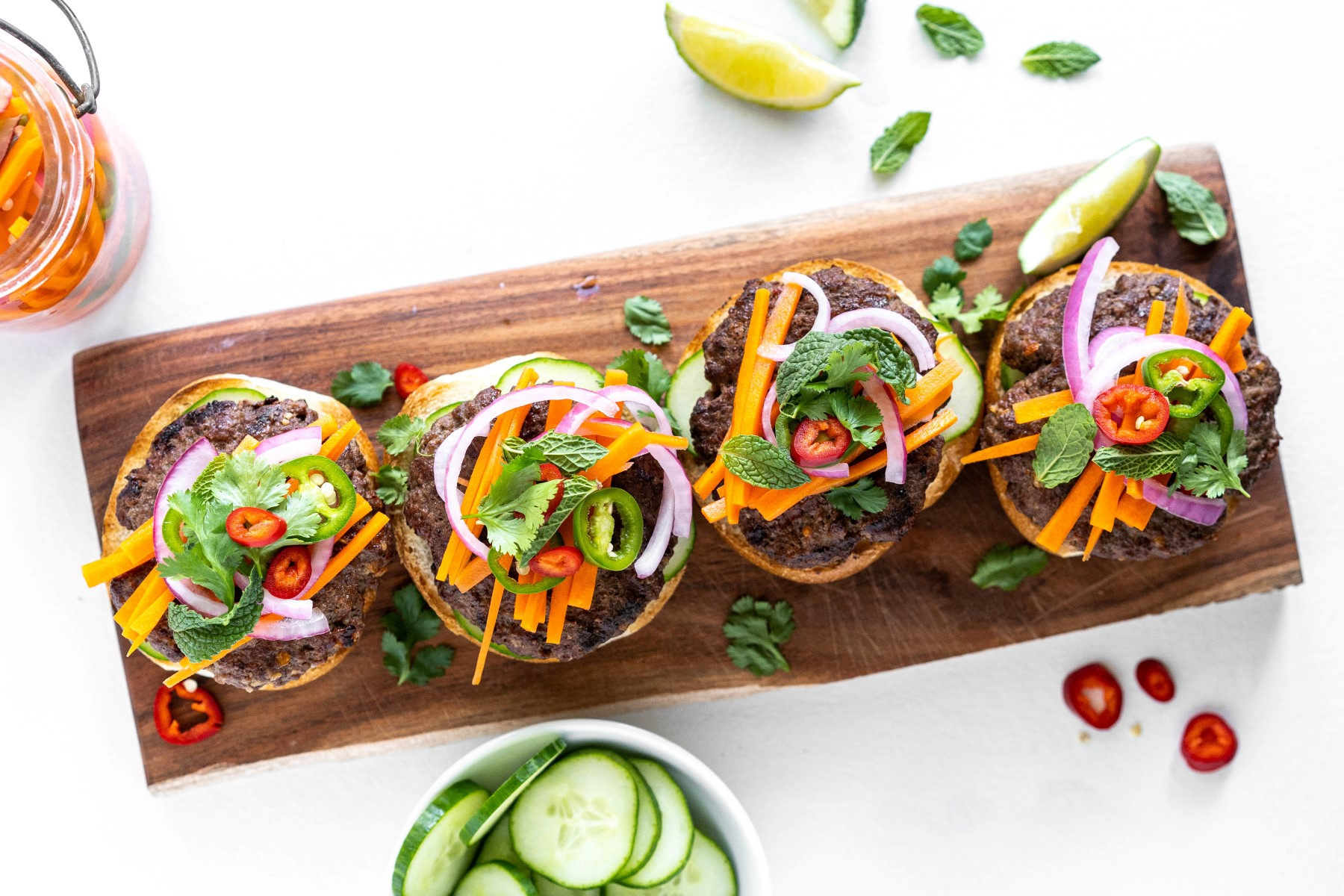 4 Banh Mi Burgers on a wooden board topped with quick pickled veggies, sliced cucumber, mint leaves and cilantro.