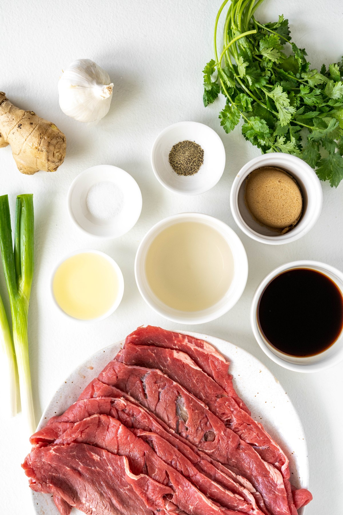 The ingredients for grilled teriyaki beef kabobs in small bowls with the raw beef on a platter