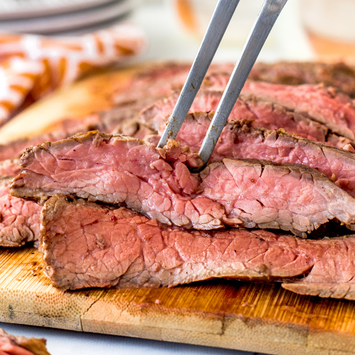 Thinly sliced Grilled Flank Steak on a wooden board with a large fork.