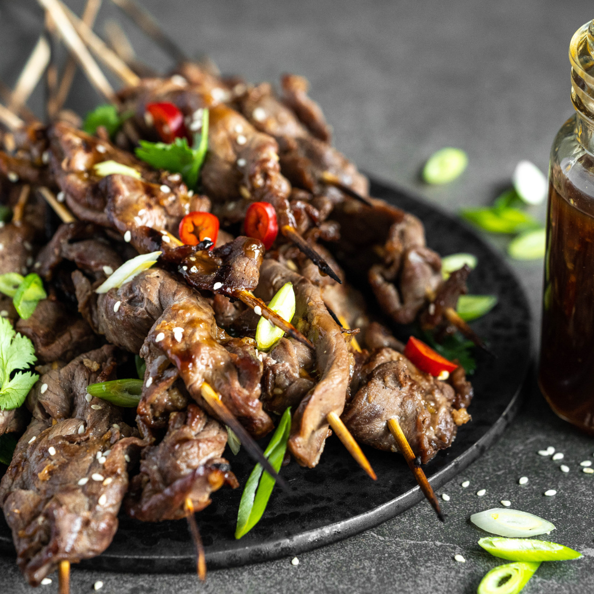 Grilled Beef Teriyaki Skewers on a black plate with sliced green onions and red chili pepper on top.