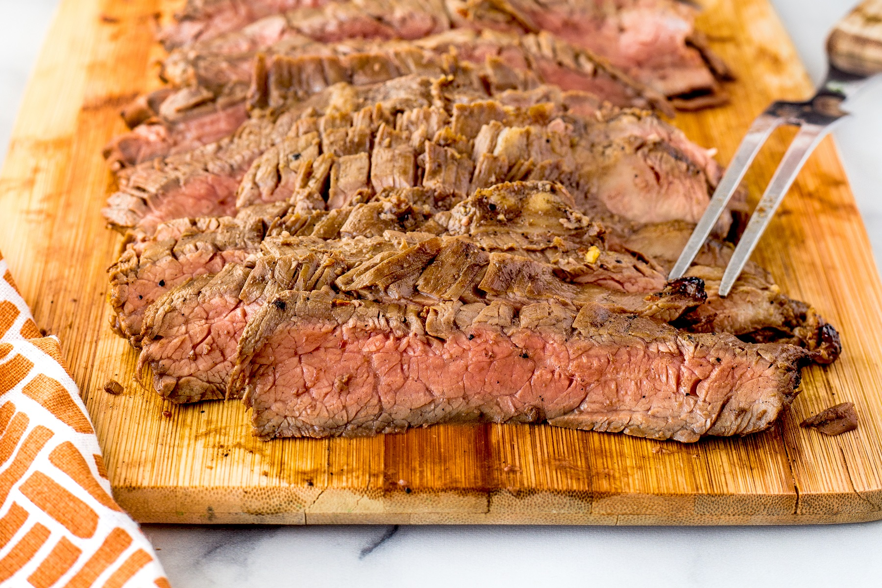 Thinly sliced grilled flank steak on a wooden cutting board
