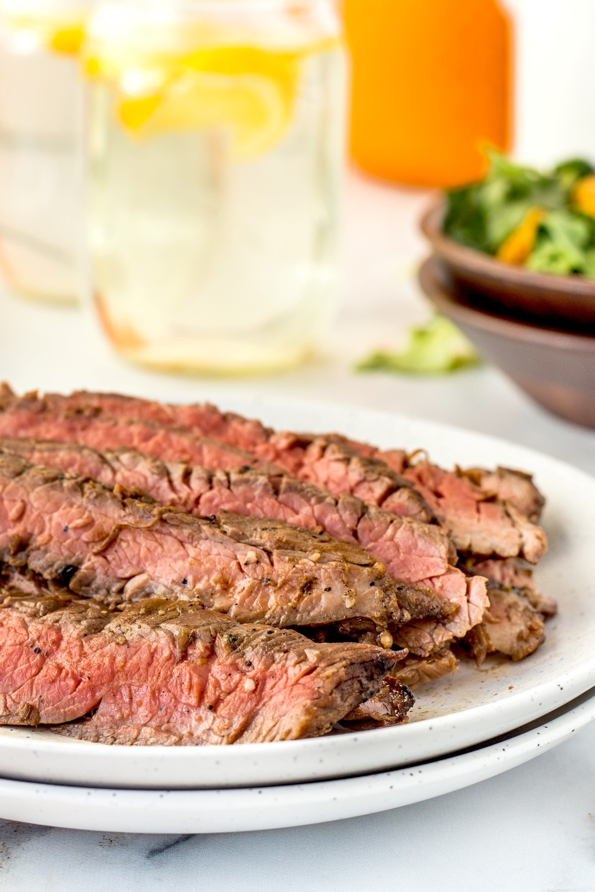 Thinly sliced grilled flank steak on a white plate.