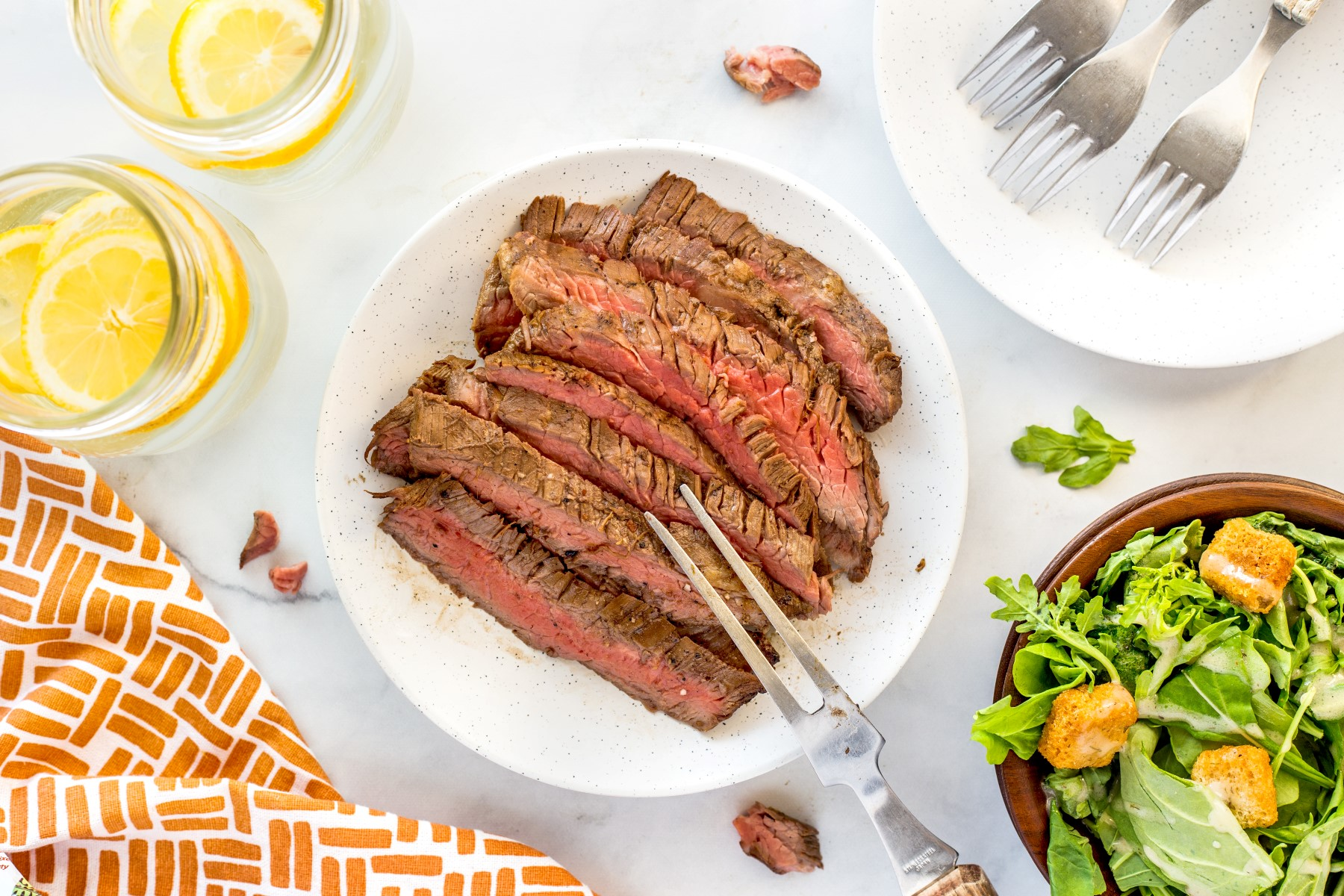 Thinly sliced grilled flank steak on a white plate with a bowl of green salad beside the plate.