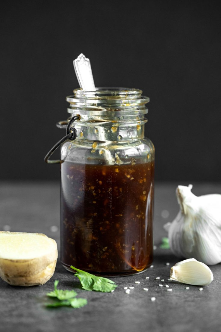 homemade teriyaki sauce in a glass jar with ginger and garlic beside the jar