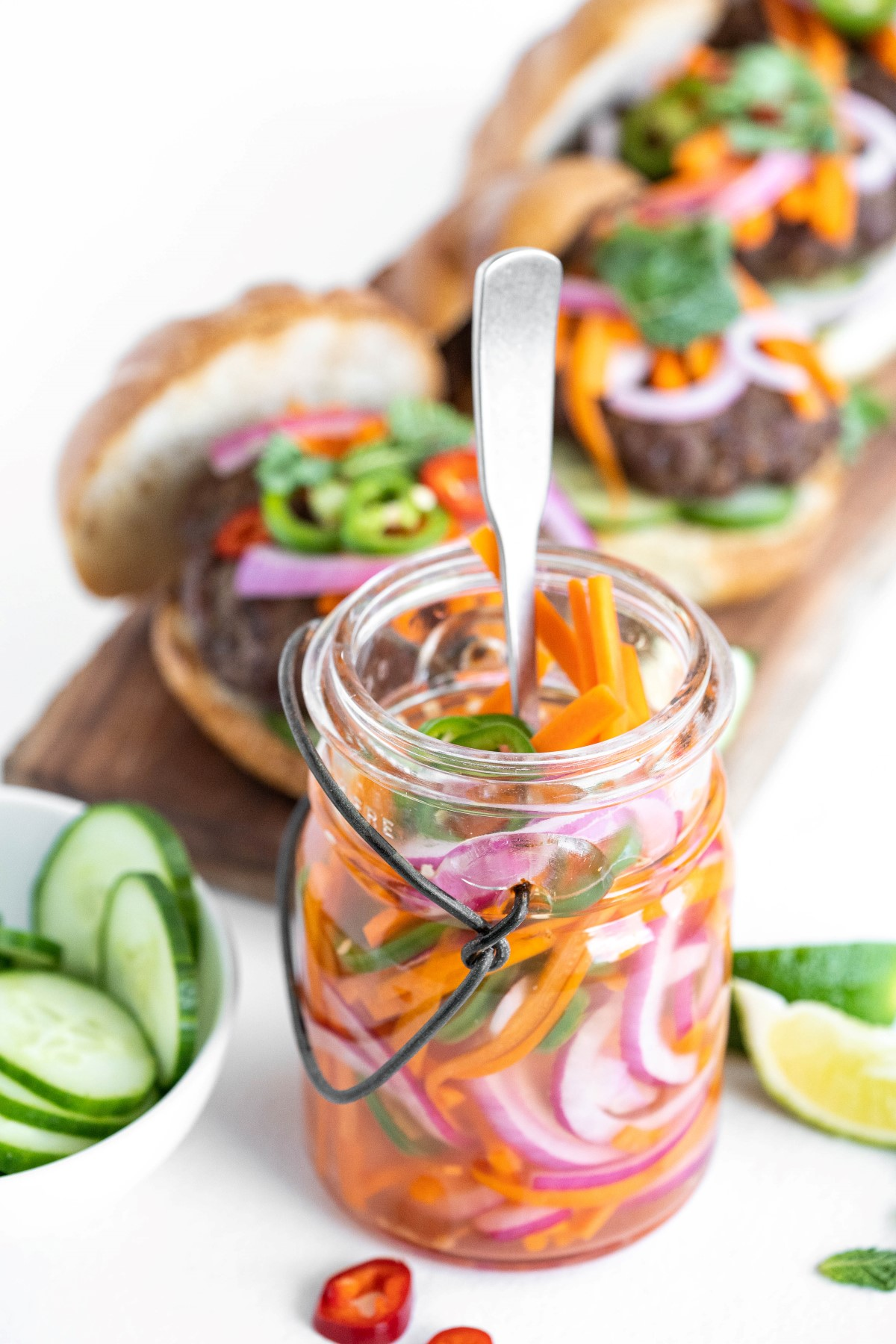 Jar of quick pickled vegetables with a fork in the jar and 2 burgers topped with pickled veggies in the background.