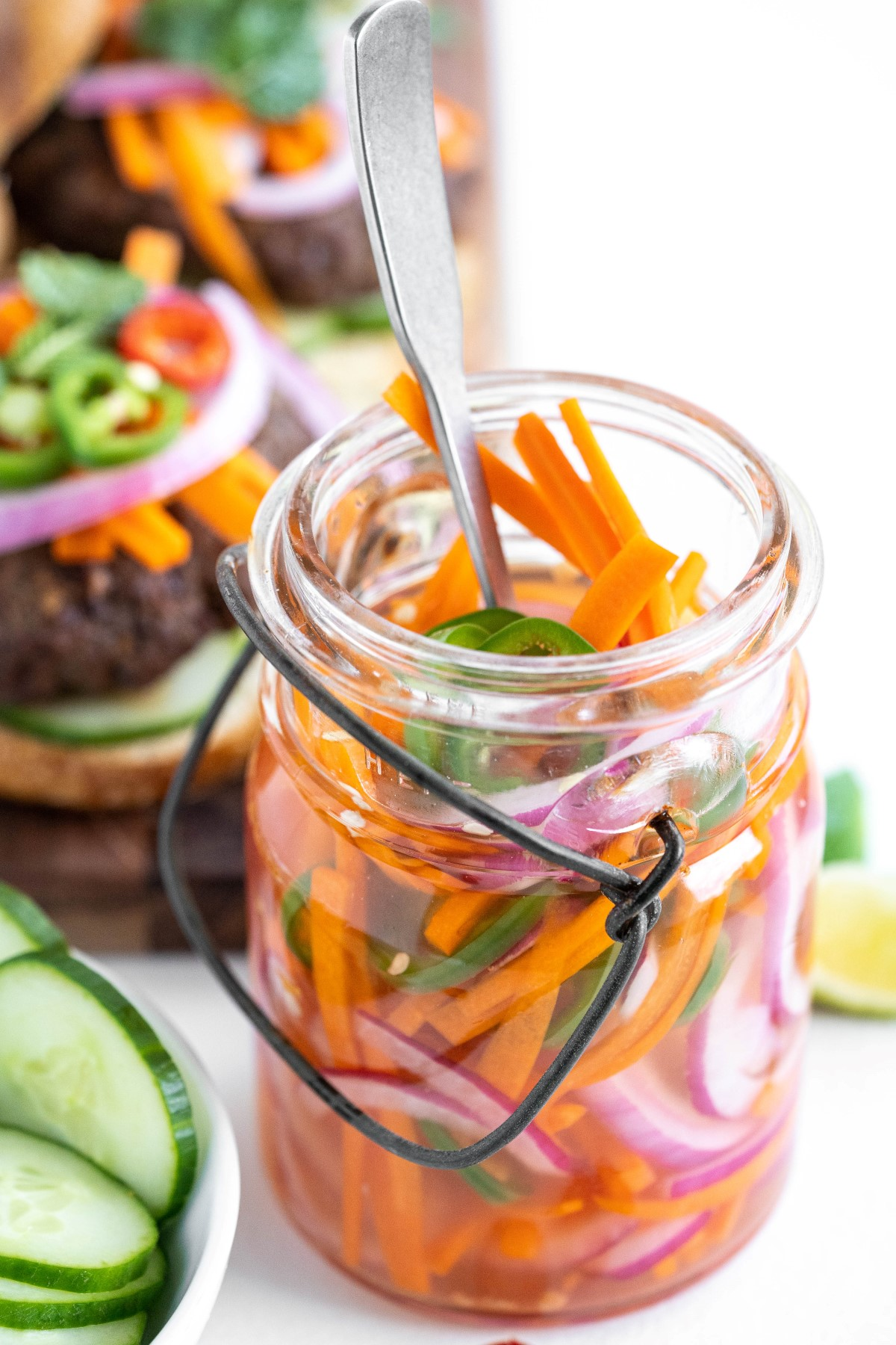 Jar of quick pickled vegetables with a fork in the jar and a burger loaded with pickled veggies in the back ground.