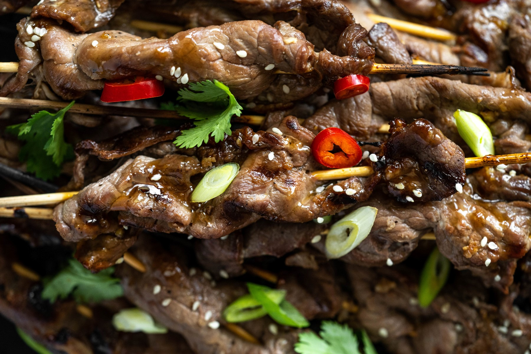 Grilled Teriyaki beef kabobs garnished with sesame seeds, chopped green onions, and sliced red chili peppers, with cilantro leaves.