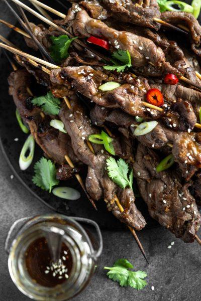 Grilled Beef Teriyaki Skewers on a black platter with a jar of teriyaki sauce beside the plate