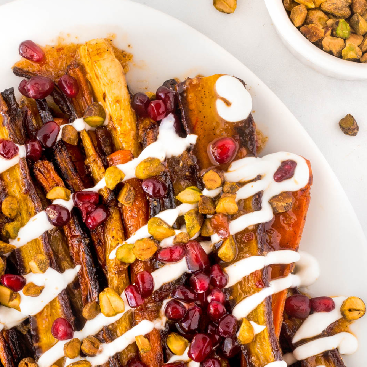 Harissa grilled carrots on a white plate with yogurt drizzled on top and pistachios and pomegranate seeds on top