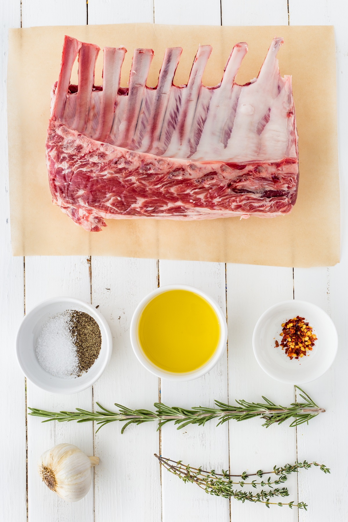 Ingredients for grilled lamb chops laid out on a white tabletop.