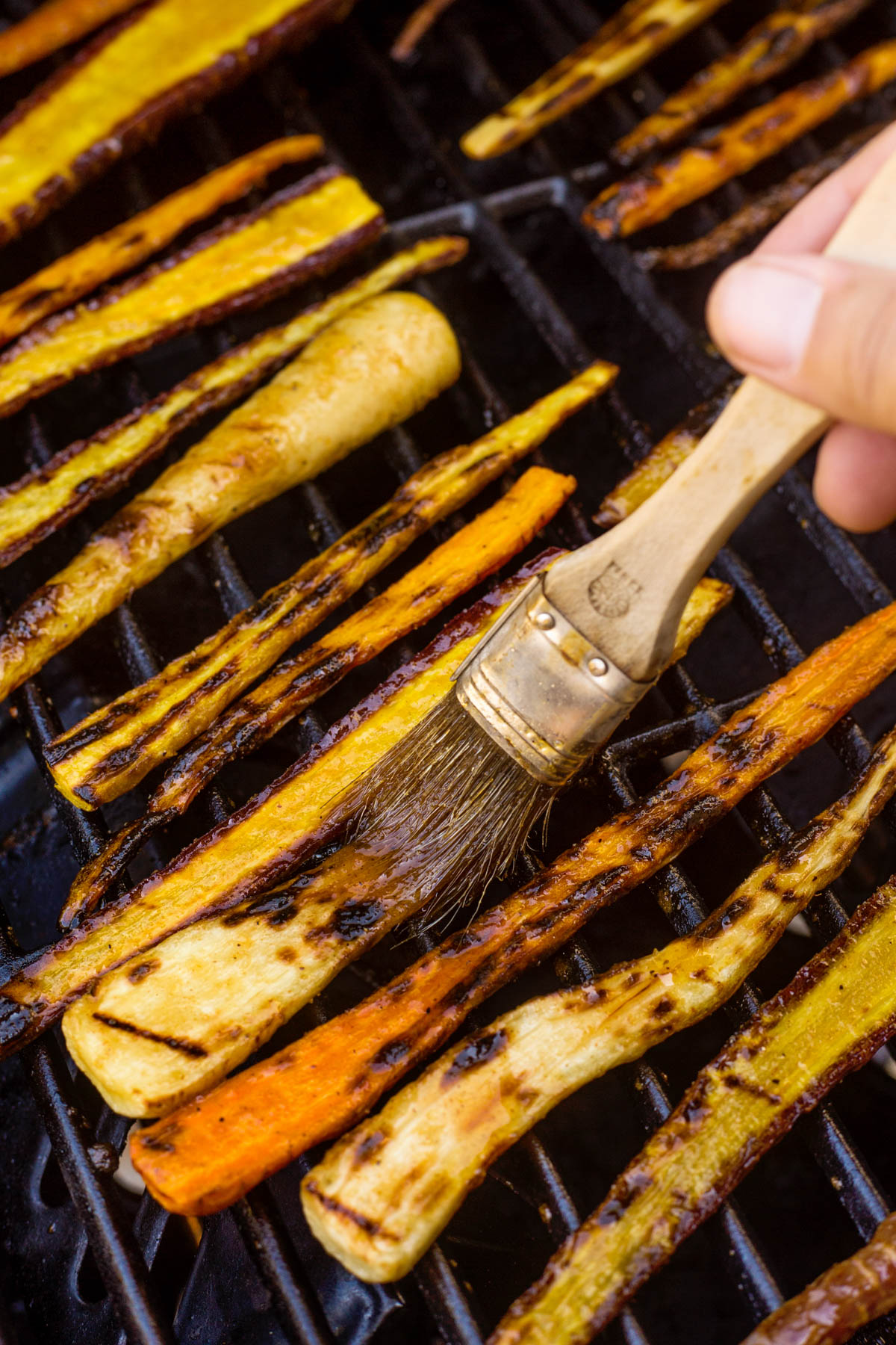 Brushing the harissa glaze on the carrots that are grilling on the BBQ