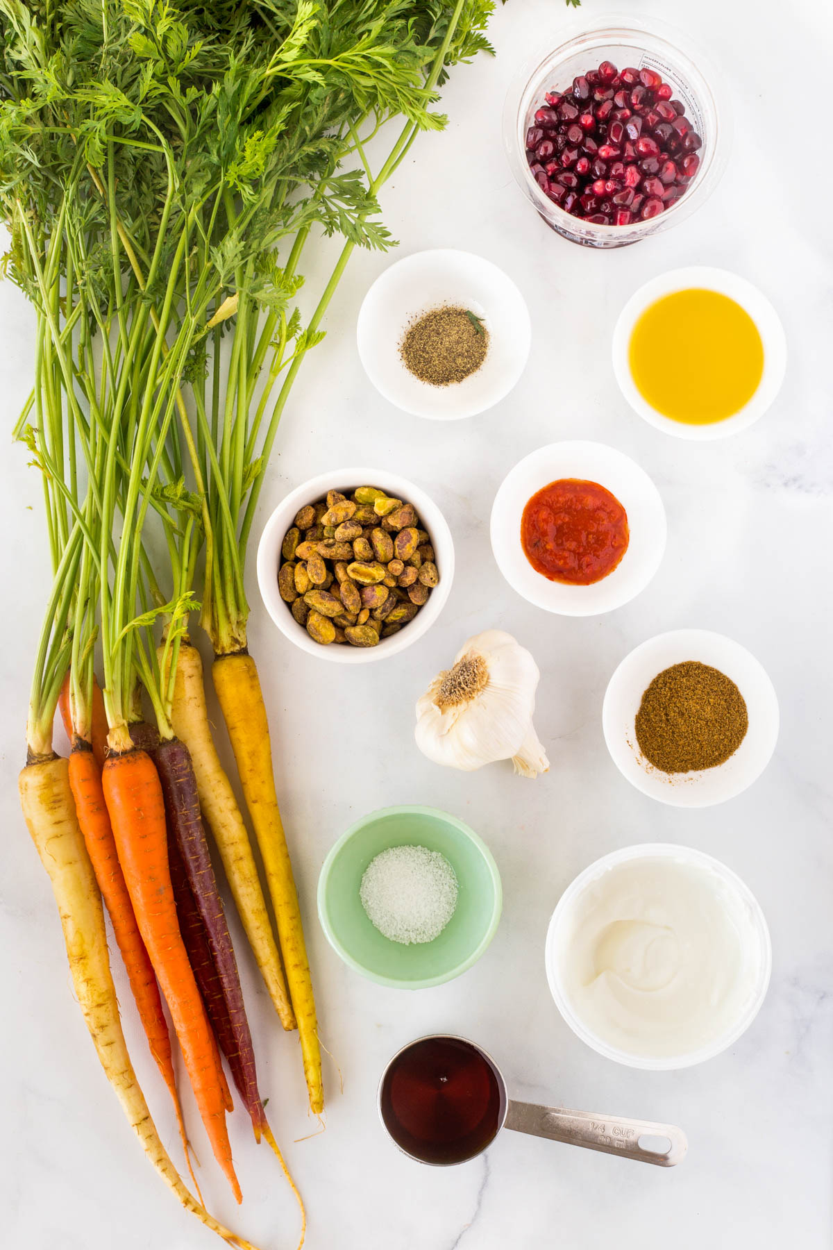 All ingredients to make harissa grilled carrots on a white countertop