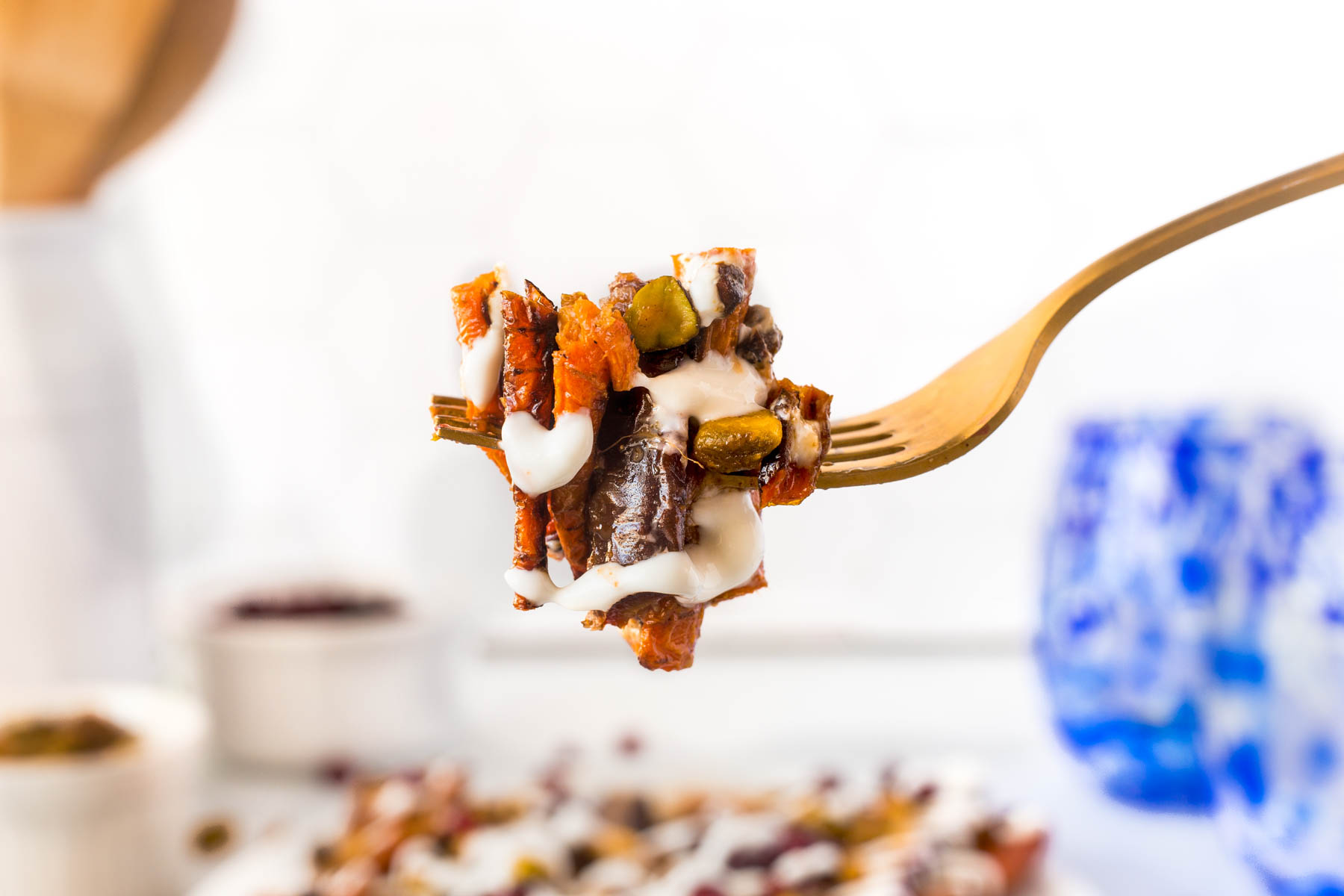 A fork full of Harissa grilled carrots with the plate of carrots in the background.