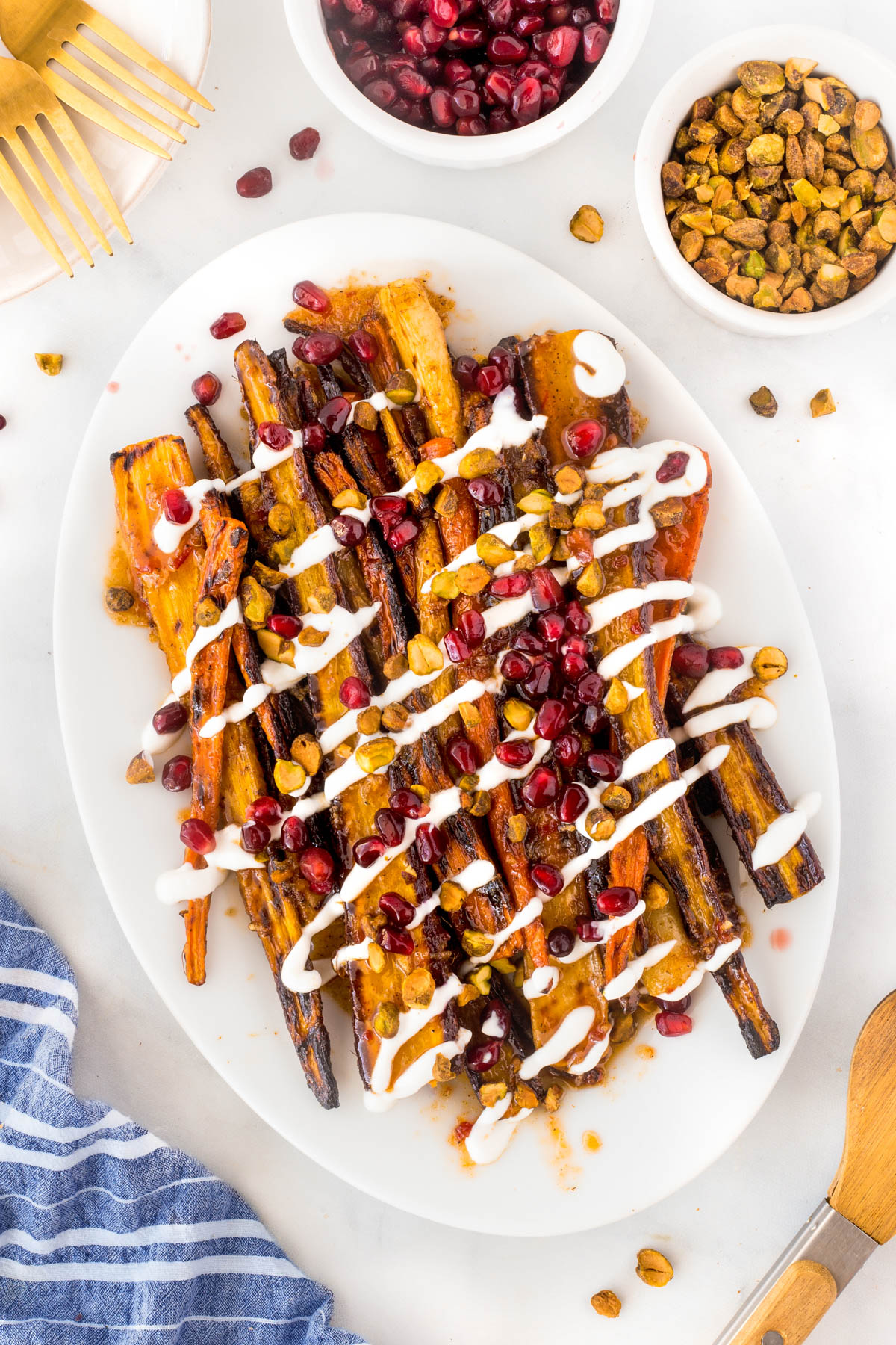Harissa grilled carrots on a large white platter drizzled with yogurt and covered with chopped pistachio nuts and pomegranate seeds.