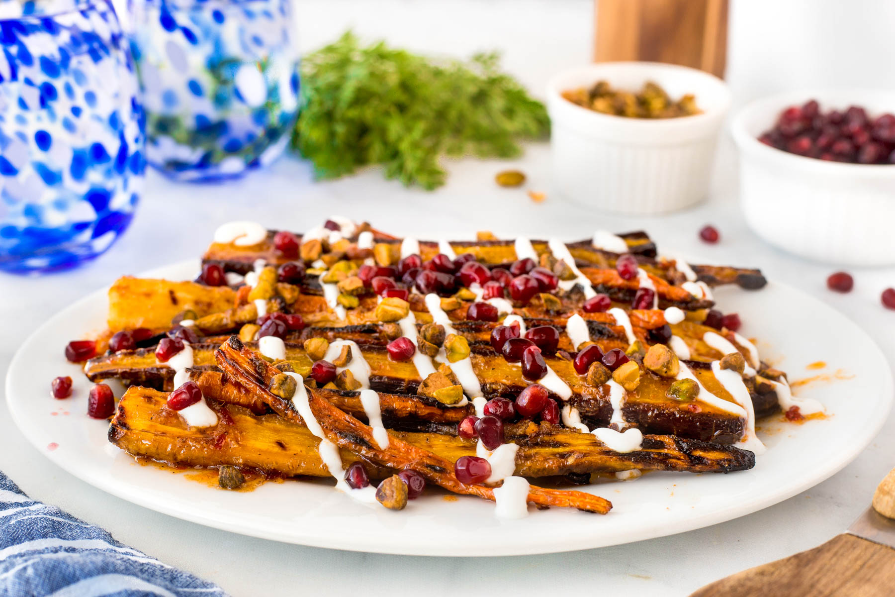 Harissa grilled carrots on a large white platter drizzled with Greek yogurt and sprinkled with pistachios nuts and pomegranate seeds.