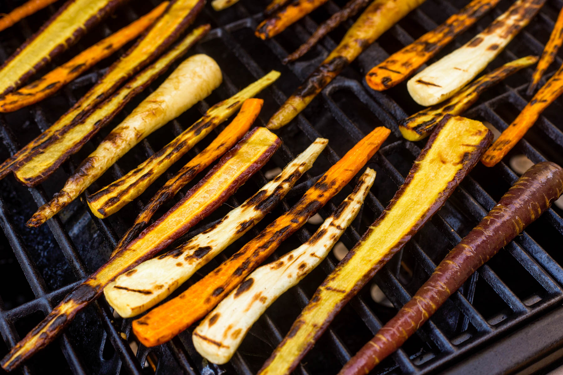 Sliced harissa grilled carrots cooking on a hot grill.