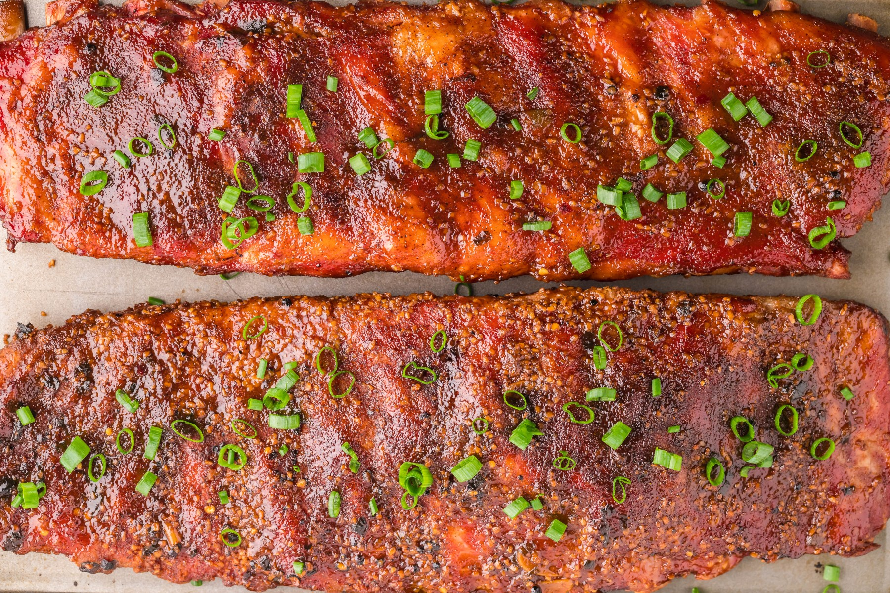 2 smoked racks of ribs garnished with chopped green onion on a parchment lined tray.