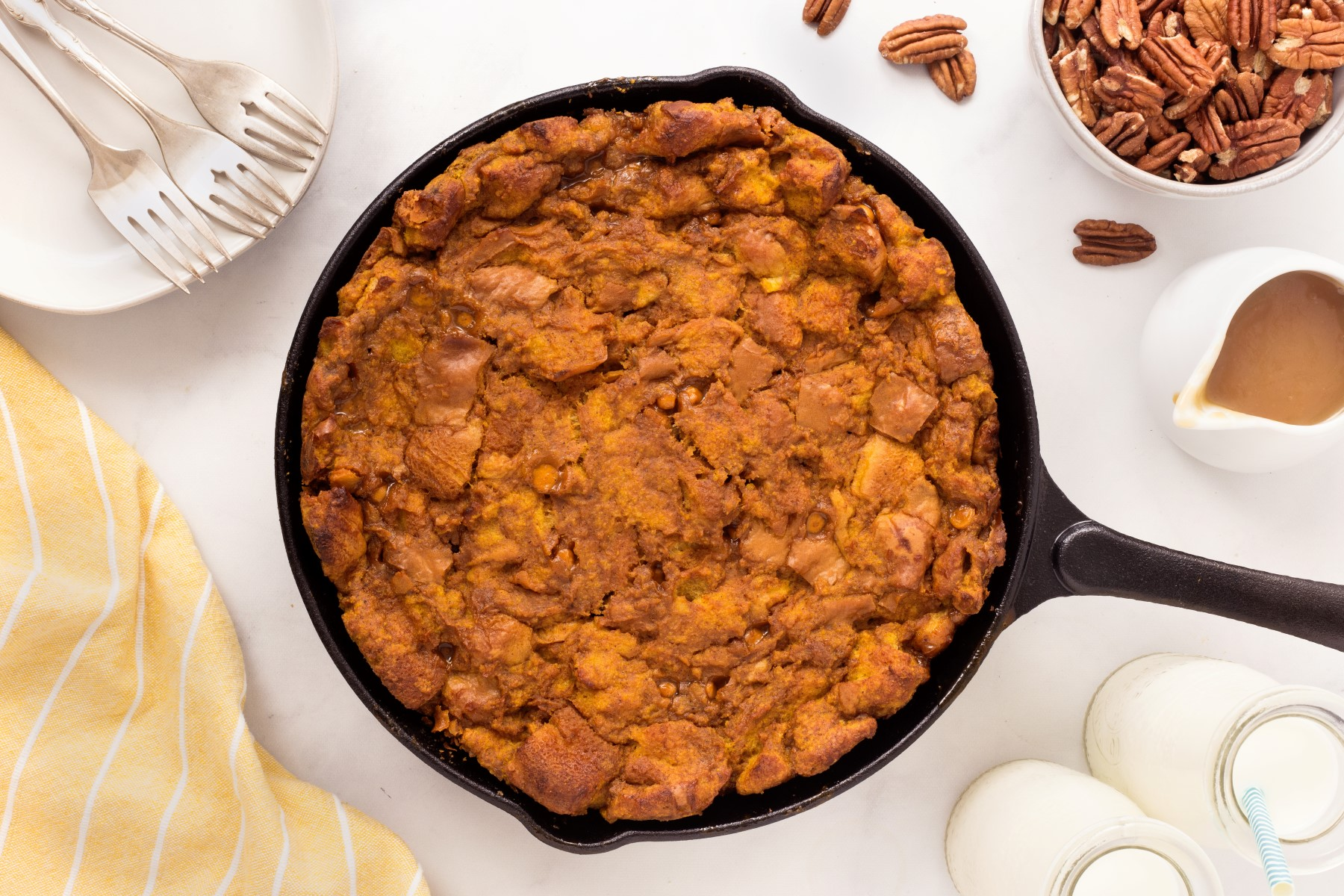 Cooked smoked bourbon pumpkin bread pudding in a cast iron pan on a white table.