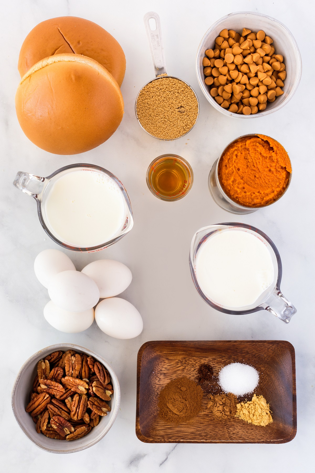 Ingredients for smoked bourbon pumpkin bread pudding laid out in small bowls on a white countertop.