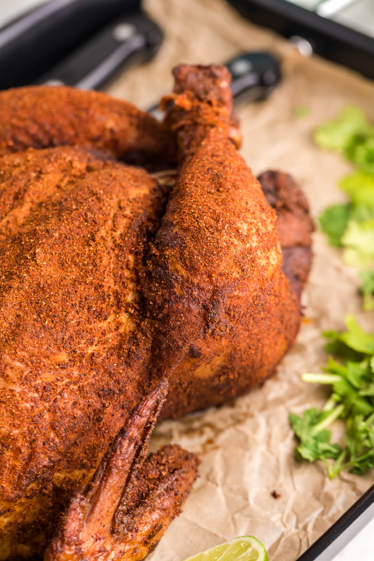 Whole smoked chicken on brown paper covered in dry rub.
