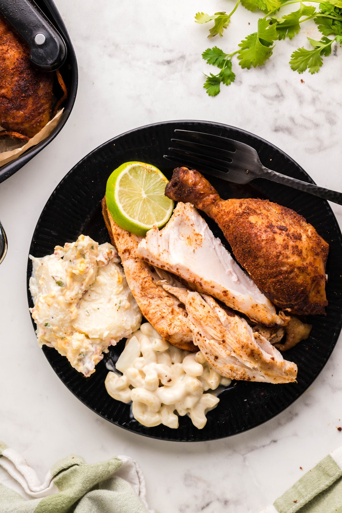 Smoked chicken drumstick and sliced breast meat on a black plate with potato salad and macaroni salad.