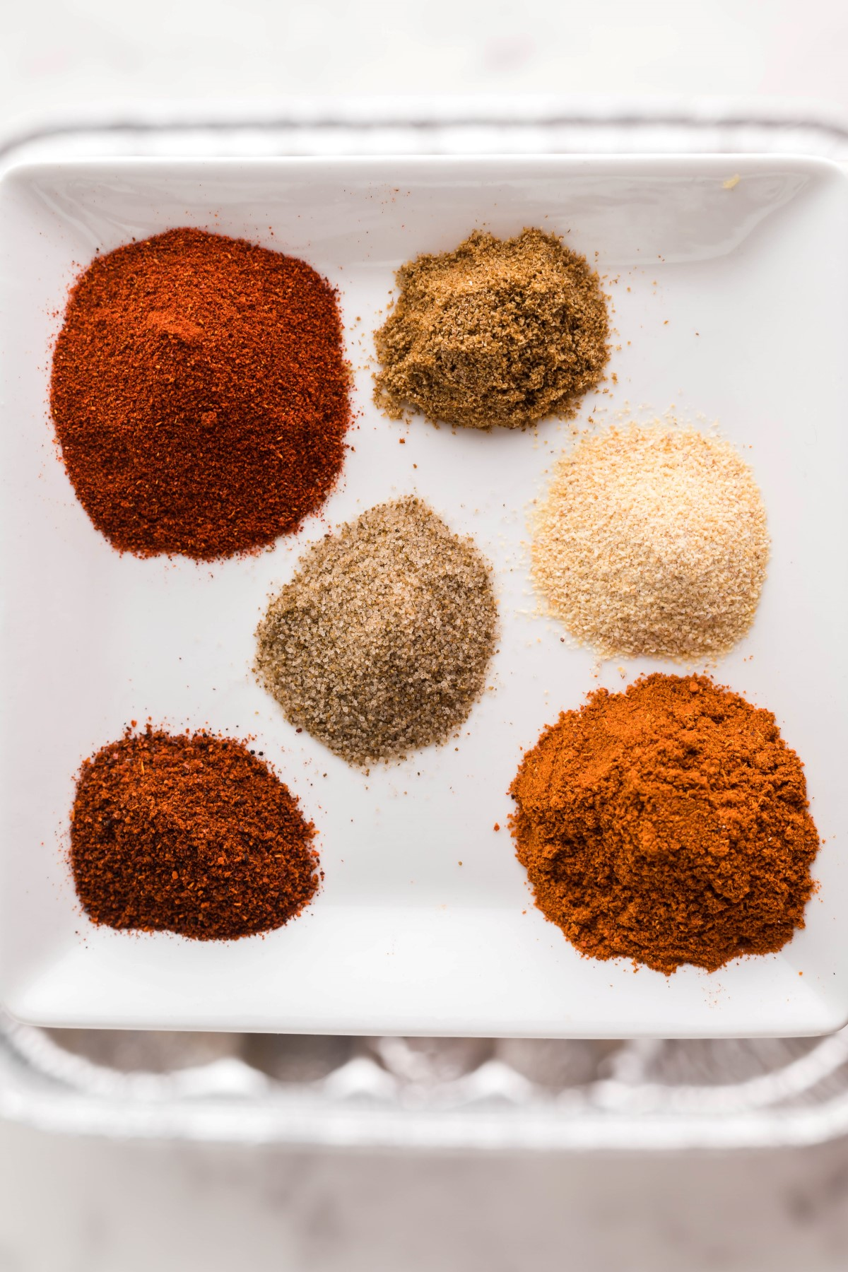 All the ingredients for the dry rub in small piles on a white plate.