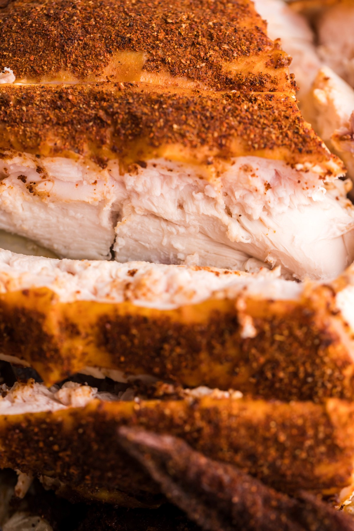 Close up of picture of smoked chicken breast slices with dry rub on the skin.